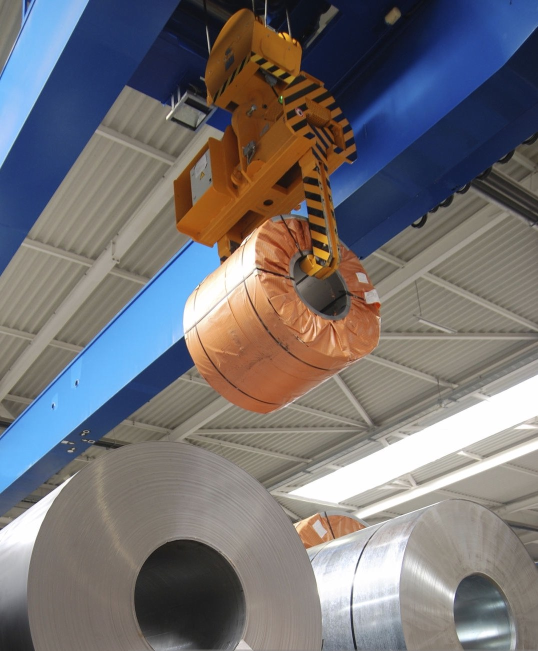 Crane lifting rolls of sheet steel in a warehouse/factory. Please see related pictures: